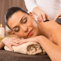 Beautiful Young Woman Receiving Hot Stones Massage At Day Spa